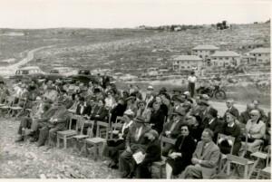 קהל המוזמנים לטקס. ברקע שכונת נווה שאנן.