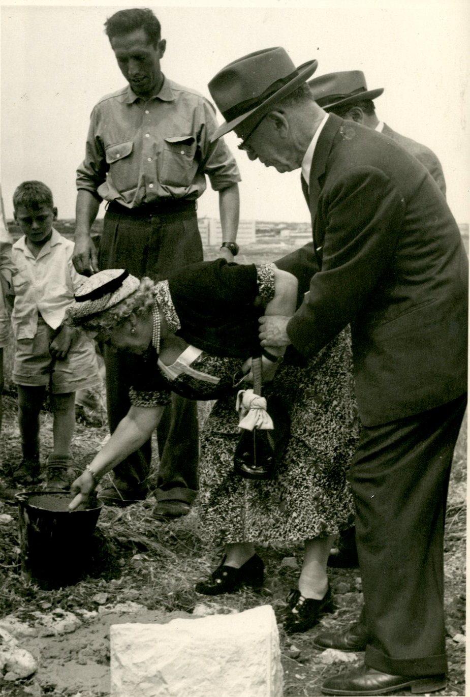 בני הזוג זלצמן יוצקים את אבן היסוד לבית האקדמיה.