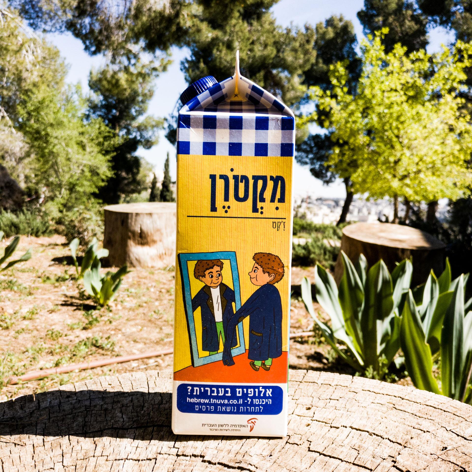 צילום קרטון חלב ועליו איור מילה מחודשת ז'קט-מקטרן