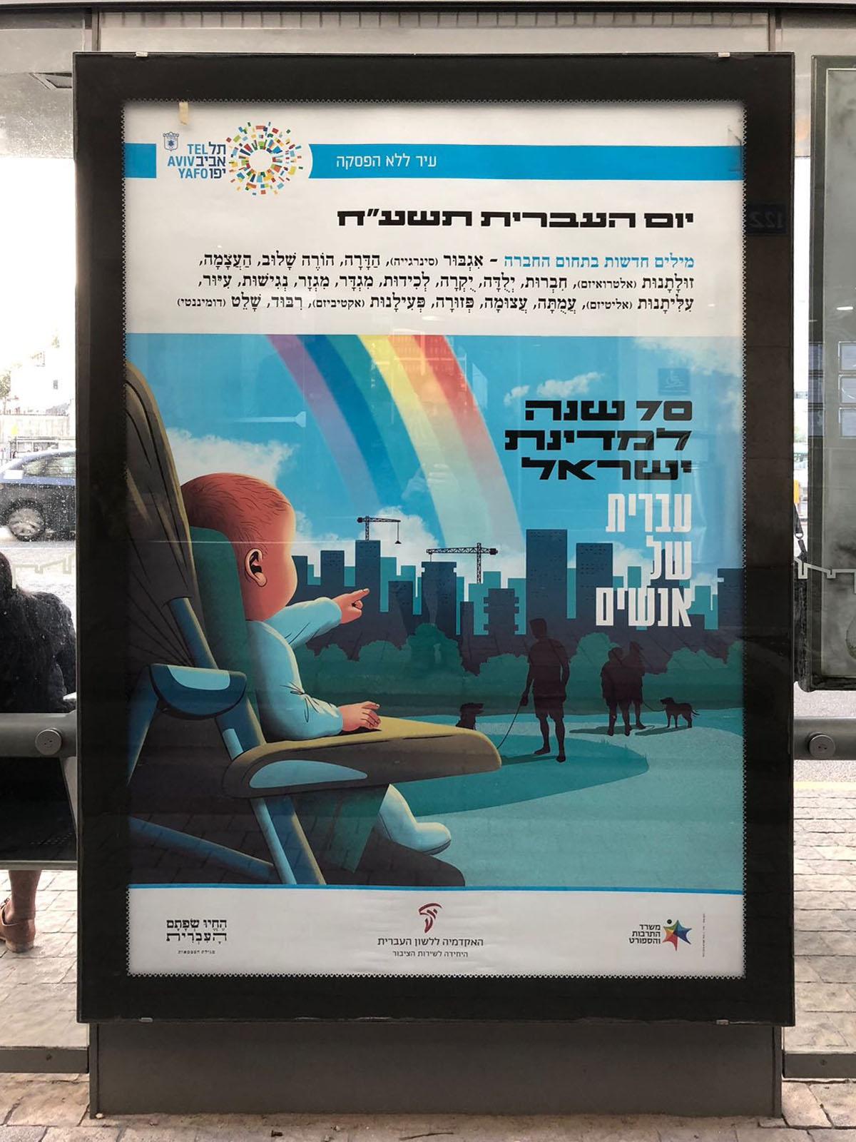 """צילום כרזה ליום העברית תשע""""ח איור של תינוק בכיסא ילדים מצביע על עיר וכלבים בפארק וכיתוב """"עברית של אנשים"""""""