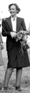 צילום של לאה גולדברג עומדת ובידה זר פרחים