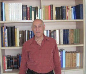 תמונתו של פרופסור אלישע קימרון ומאחוריו כוננית ספרים (צילום: צחי לרנר)