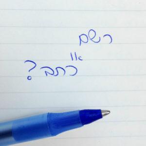 עט מונח על נייר והכיתוב: רשם או כתב?